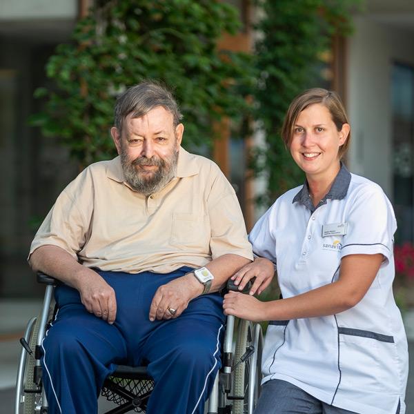 Mann im Rollstuhl mit Pflegehilfe